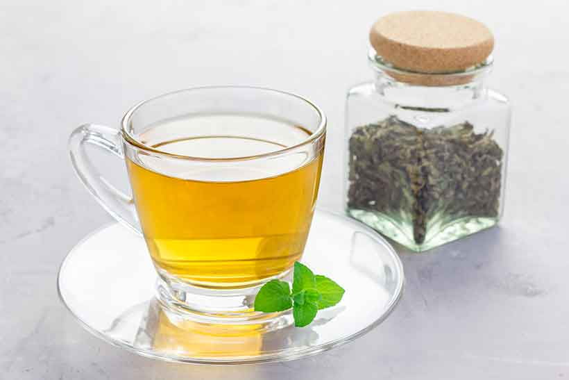 Glass Cup of Peppermint Tea Next To Dried Peppermint Leaves.