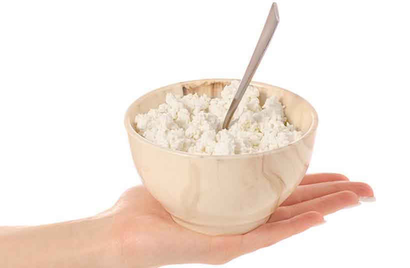 A Woman Holding a Bowl of Cottage Cheese In Her Hand.