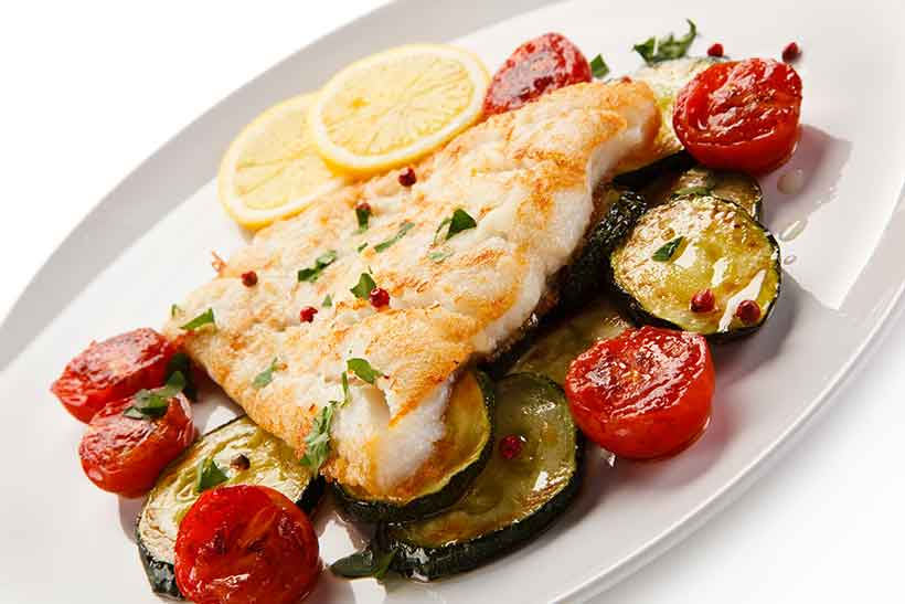 A Roasted Cod Fillet On a Plate With Zucchini Slices and Cherry Tomatoes.