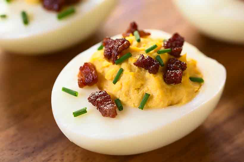 Devilled Eggs With Bacon Pieces and Chopped Chives.