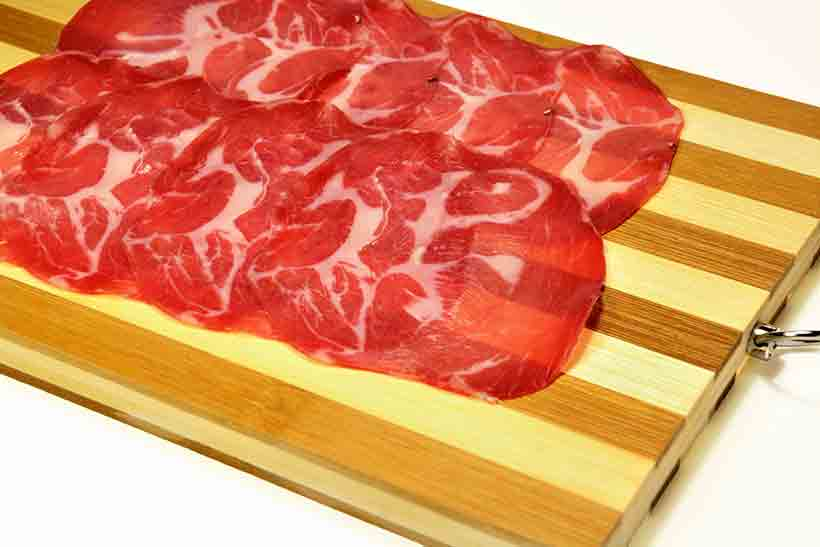 Slices of Coppa (Cured Meat) On a Wooden Board.