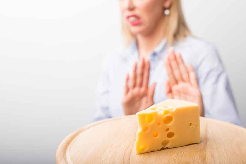 A Woman Making a Gesture Saying She Doesn't Want Cheddar Cheese.