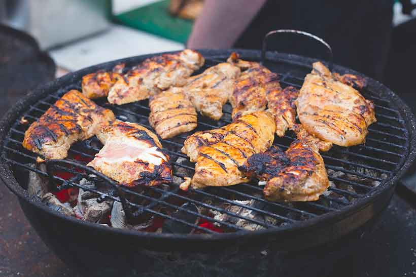 Turkey Steaks Covered In a Curry Yogurt Marinade On a BBQ Grill.