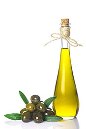 A Bottle of Extra Virgin Olive Oil Next To Some Olives.