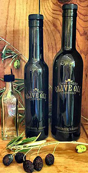 A Dark Black Bottle of Cave Creek's Ultra Premium Extra Virgin Olive Oil.