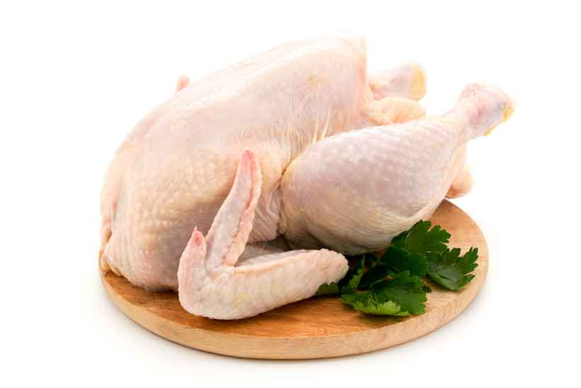 A Whole Uncooked Chicken On a Wooden Board.