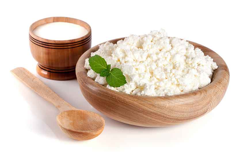 A Wooden Bowl Containing Cottage Cheese - a Fresh Dairy Product.