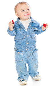 A Young Child Holding and Eating Strawberries.