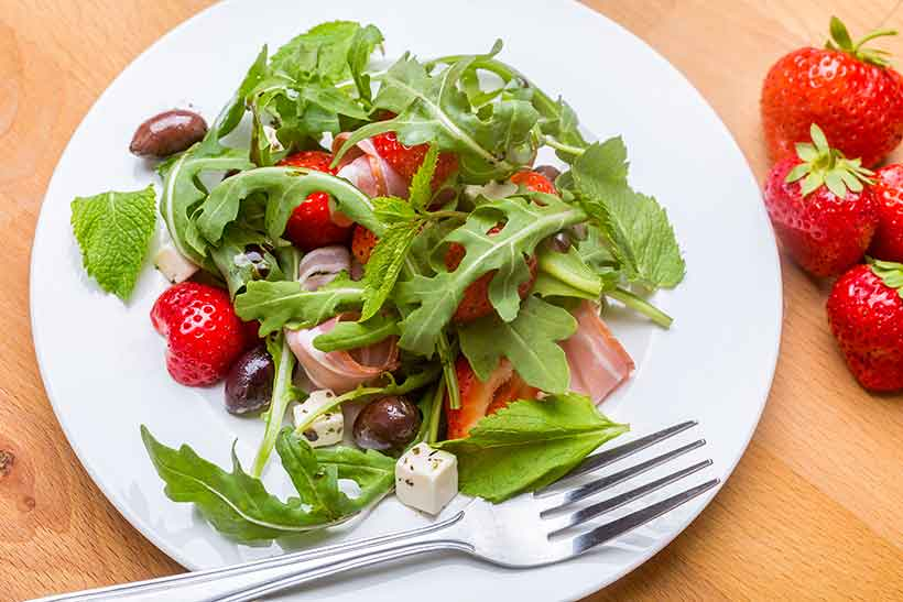 A Greek Salad Featuring Ham, Strawberries, Feta, Salad and Kalamata Olives.