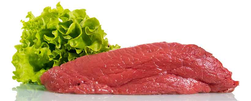 Picture of Uncooked Veal Meat Next To Some Lettuce.
