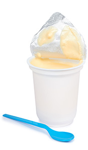 An Open Pot of Yogurt With a Spoon.