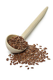 A Pile of Brown Flaxseeds and in a Wooden Spoon.