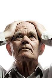 An Elderly Man With Dementia Holding His Head in Despair.