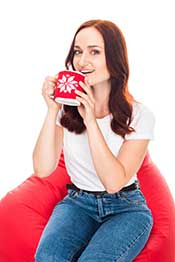 A Woman Sat Down Smiling With a Cup of Black Tea.
