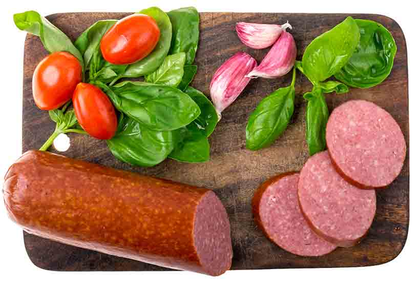 A Salami Sausage, Slices of Salami and Vegetables On a Wooden Board.