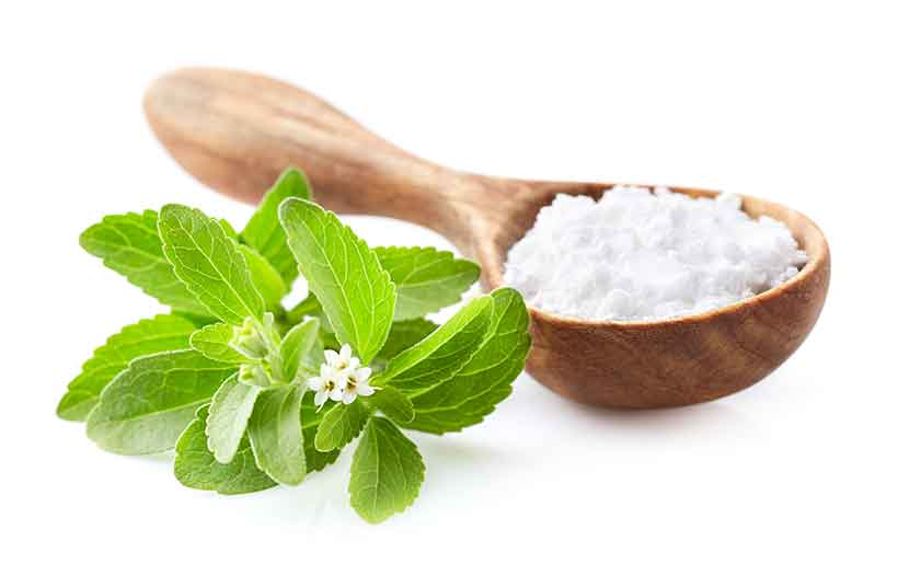 Stevia Leaves Next To the Powdered Sweetener.