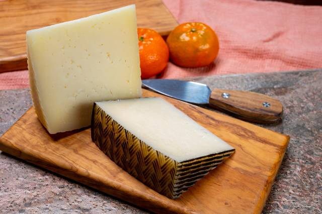 Spanish Manchego Cheese On a Wooden Board.