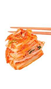 Some Chopsticks Holding Several Pieces of Kimchi.
