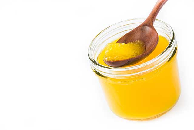 Getting a Spoon of Ghee From a Glass Jar.
