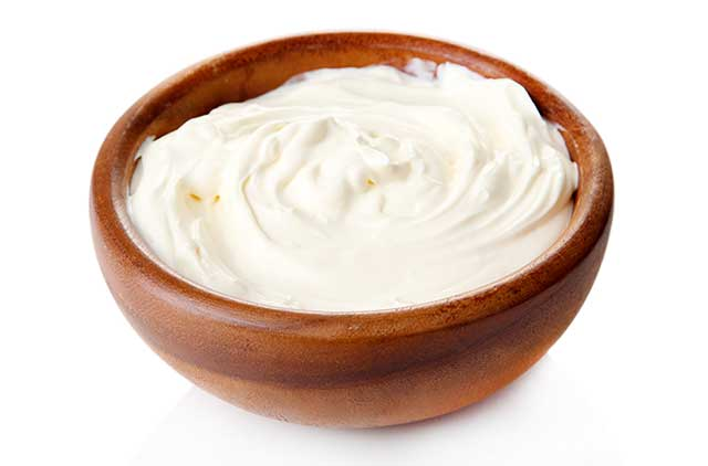 Thick Sour Cream In a Wooden Bowl.
