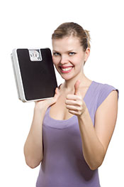 A Woman Happy After Losing Weight, Holding a Scale.