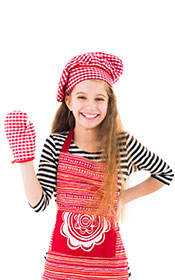 A Young Girl Wearing a Baking Glove and Baking Apparel.