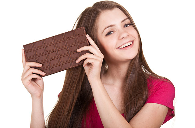 Young Woman Eating Dark Chocolate With a Happy Smile.
