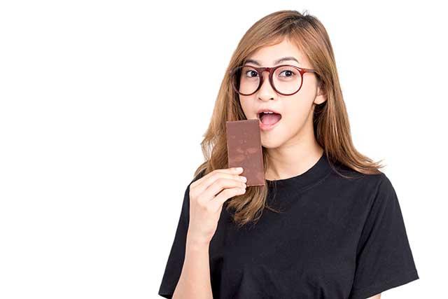 Asian Woman Craving a Chocolate Bar.