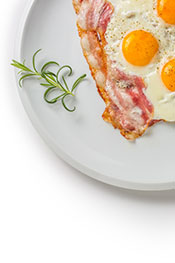 Bacon and Eggs On a White Plate.