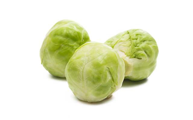 Three Brussels Sprouts On a White Background.