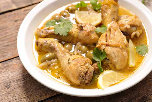 A Bowl Containing Chicken Drumsticks In a Lemon Butter Sauce.