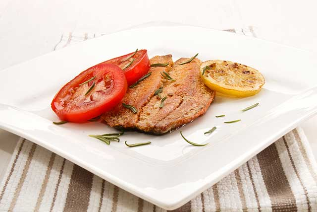 Grilled Kipper On a Plate With Lemon and Tomato.