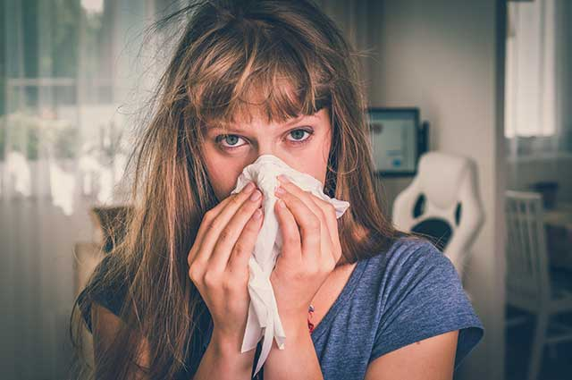 Sick Woman With Flu Using a Handkerchief.