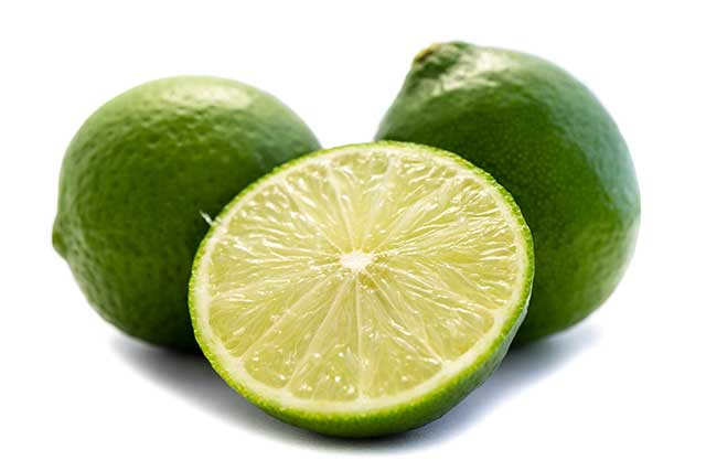 Whole Limes and a Lime Half On a White Background.