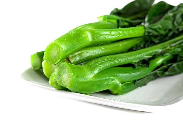 Several Stems of Gai Lan (Chinese Broccoli) On a Plate.