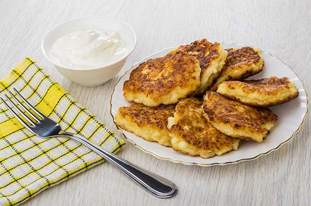 Cottage Cheese Pancakes On a Plate With Sour Cream Side.