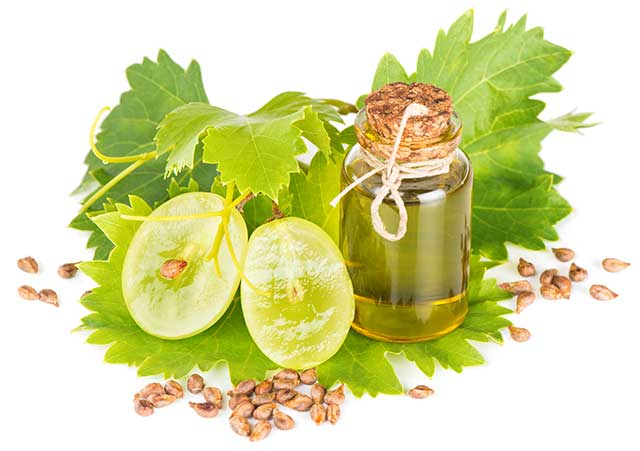 Grapeseed Oil In a Glass Bottle Next To Fresh Grapes.