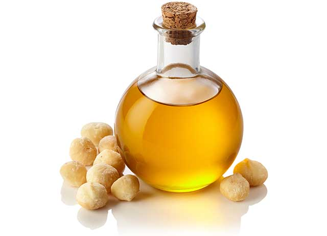 Macadamia Oil In a Glass Jug Next To Macadamia Nuts.