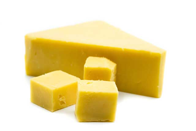 A Large Piece of Cheddar Cheese and Some Smaller Pieces.