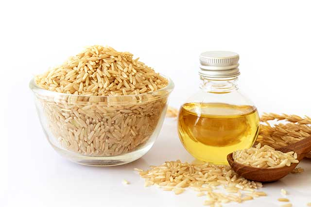 Rice Bran Oil Next To a Bowl of Brown Rice.