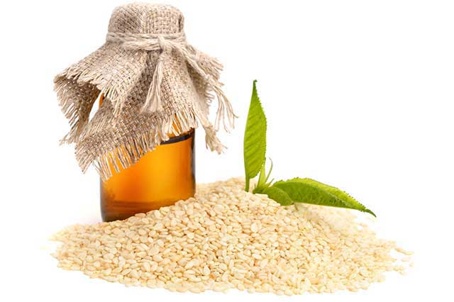 Sesame Oil Next To a Pile of Seeds.