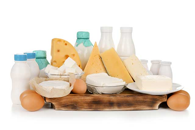 Fresh Dairy Foods and Whole Eggs On a Wooden Board.