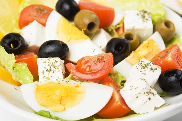 Feta Cheese Salad Featuring Eggs, Olives, Tomatoes and Lettuce.