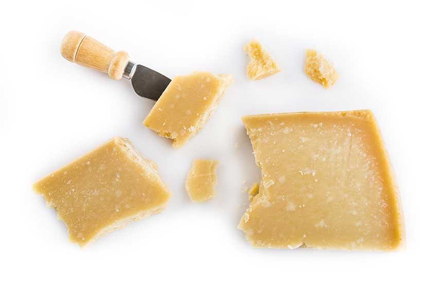 Pedazos de Parmigiano-Reggiano con un cuchillo para queso.