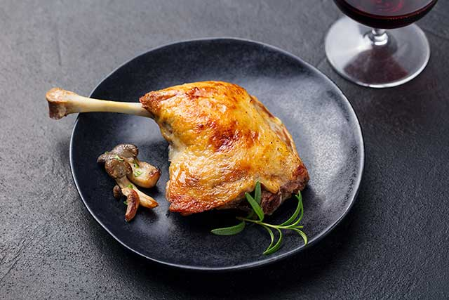 Roasted Duck Leg on a Black Plate Next To Wine.