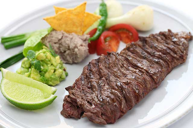 Cooked Skirt Steak On a Plate With Vegetables.