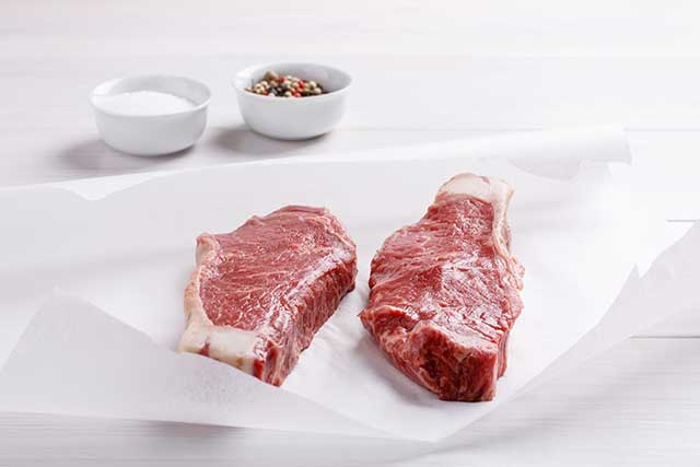 Two Raw Striploin Steaks Sitting At Room Temperature.
