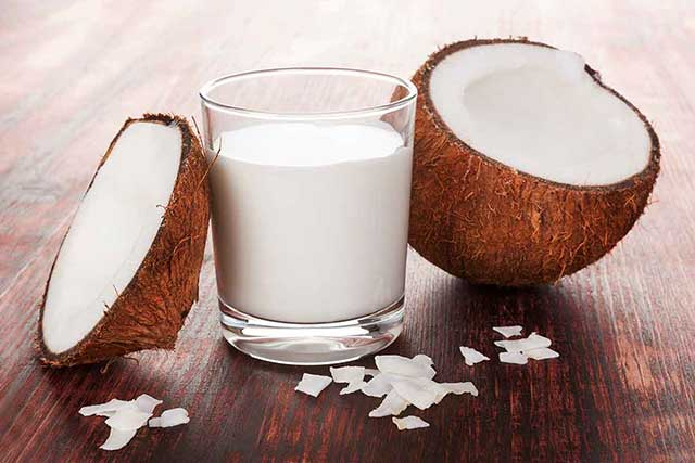 A Glass of Coconut Cream Next To Two Halves of Coconut.