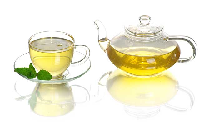 Green Tea In a Glass Cup With Glass Teapot.