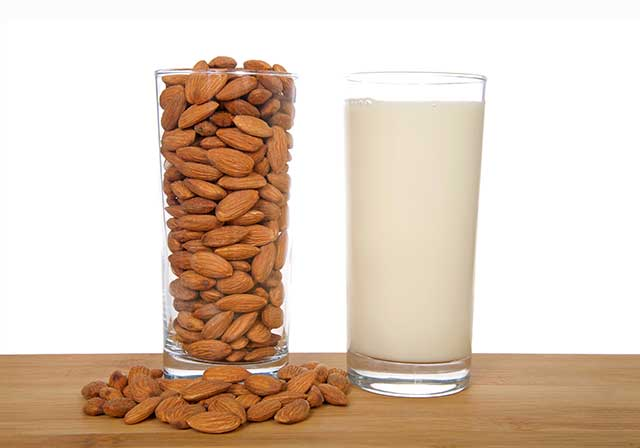 Thick Glass of Almond Cream Next To a Glass of Almonds.